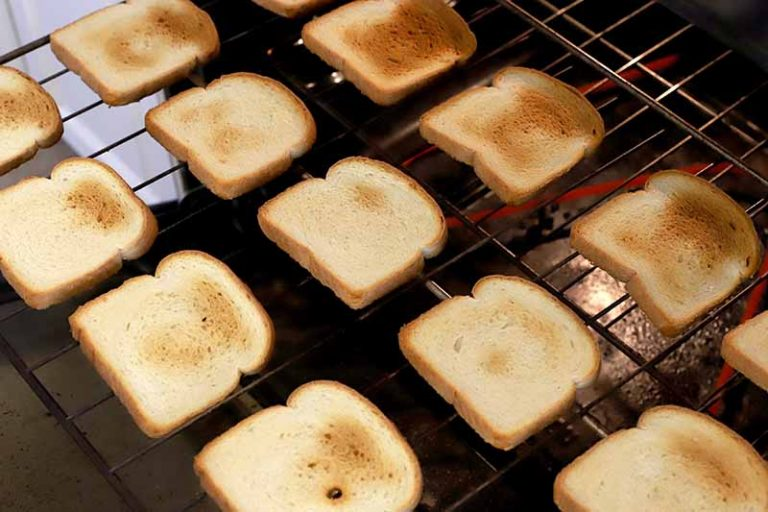Vertical image of white bread slices with different portions that are toasted golden brown, in diagonal rows on a baking rack in an oven.