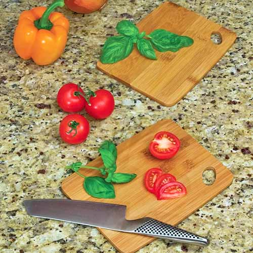 Tomatoes, basil, and bell peppers rest on and nearby two cutting boards with a knife ready for chopping.