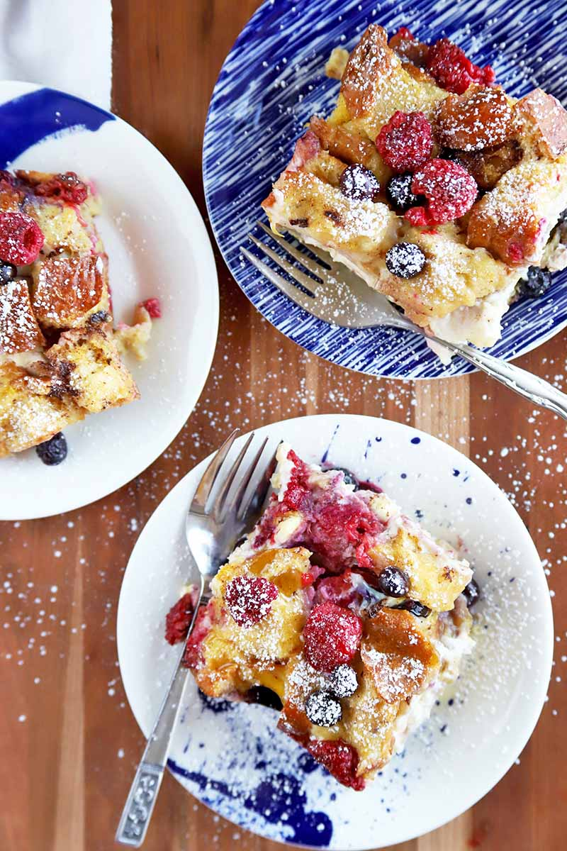 Overhead vertical image of three small blue and white patterned plates of berry breakfast bake with forks, sprinkled with powdered sugar, on a brown wood table.