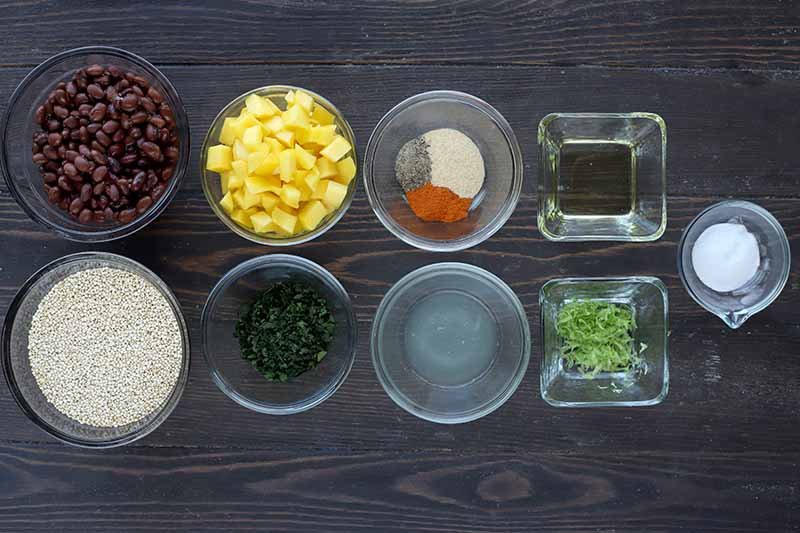 Horizontal top-down image of assorted ingredients in clear glass dishes on a dark wooden surface.