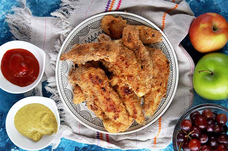 Horizontal top-down image of a plate of baked chicken fingers in the center, with condiments and fresh fruit on the sides.