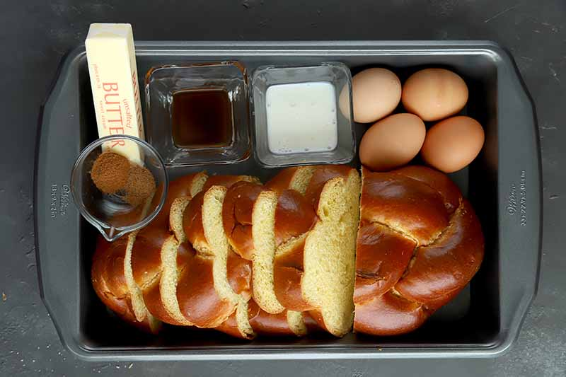 Horizontal image of sliced challah bread, eggs, butter, and other assorted ingredients in a metal pan.