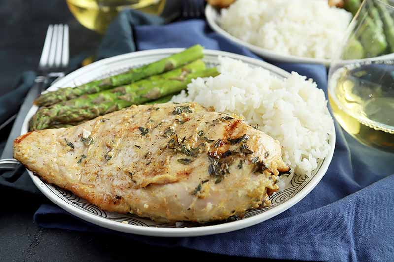 Horizontal image of a whole chicken breast seasoned with thyme next to white rice and asparagus.