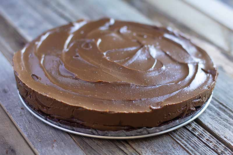 Horizontal image of a chocolate torte on the metal bottom of a springform pan.
