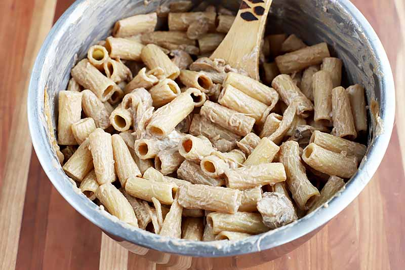 Horizontal image of rigatoni and a creamy sauce with a wooden spoon stirring the mixture.
