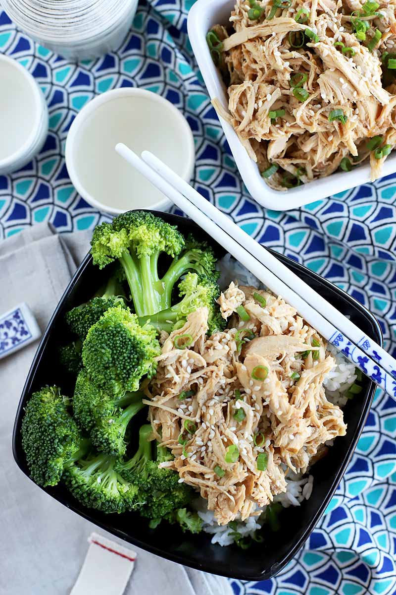 Vertical top-down image of dishes with shredded chicken and broccoli florets and white chopsticks on a patterned blue napkin.