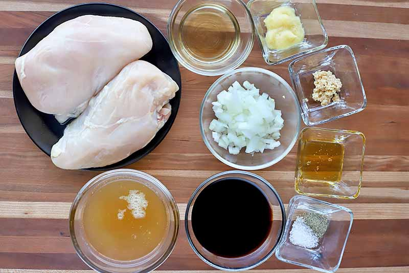Horizontal image of assorted ingredients, including raw poultry breasts, in various dark and clear dishes on a wooden surface.