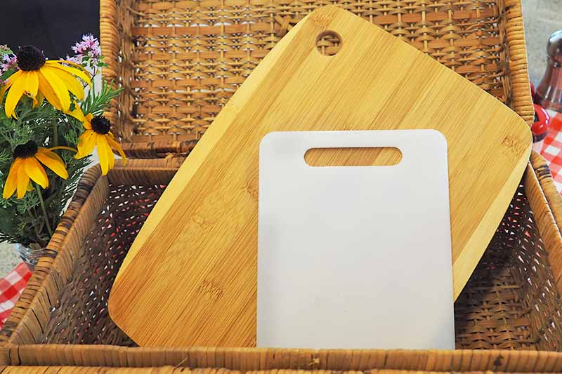 Two cutting boards rest in a picnic basket with flowers decorating.