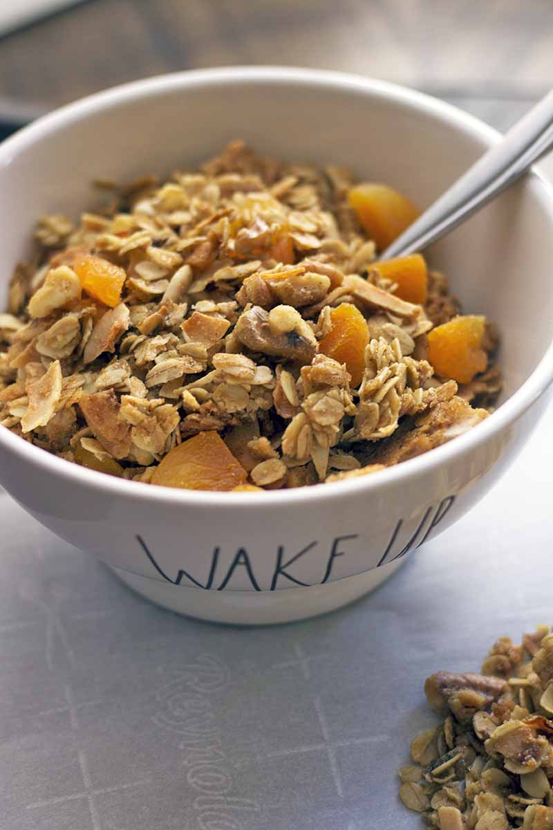 "Vertical closely cropped image of a white cereal bowl that says ""Wake Up"" on the front, filled with apricot granola with a spoon, on a white parchment paper surface with a small pile of the breakfast food to the right, on a brown wood surface."
