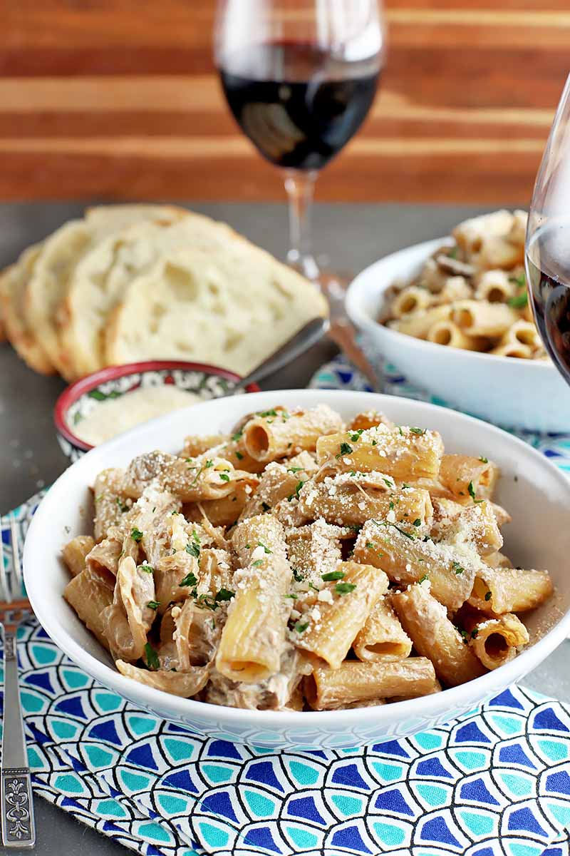 Vertical image of two white bowls with cooked pasta and garnishes, next to bread slices and a glass of red wine.