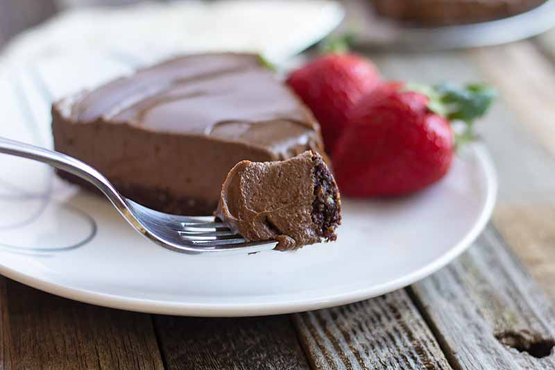 Horizontal image of a fork holding a piece of chocolate dessert in front of the whole slice on a white plate with strawberries.