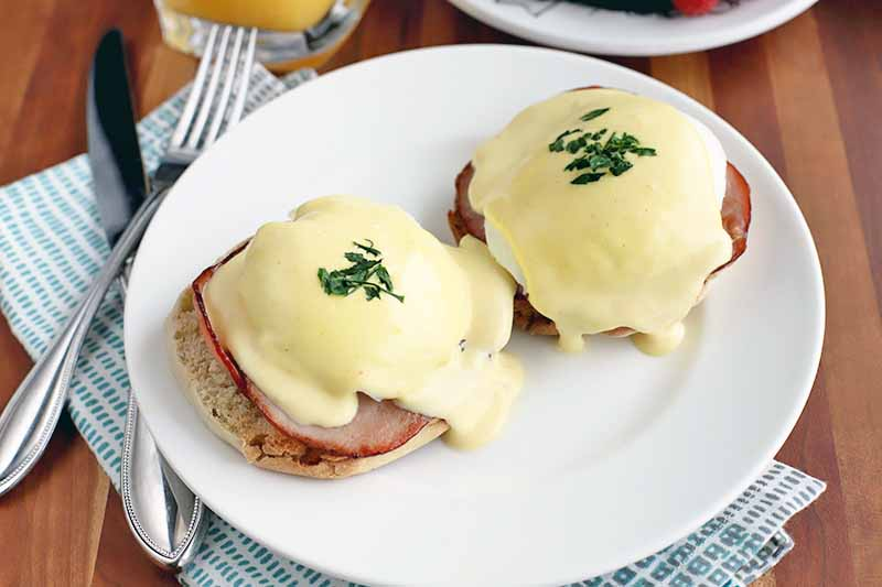 Horizontal overhead image of homemade eggs Benedict on a plate with a folded cloth napkin and silverware, and a glass of juice and a bowl of fruit in the background, on a brown wood table.