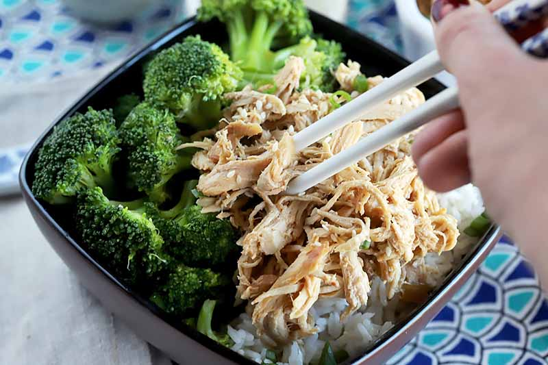 Horizontal image of a hand holding white chopsticks picking up a pile of shredded chicken in a bowl with broccoli.