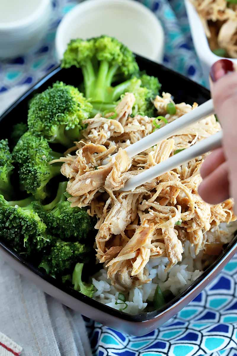 Vertical image of a hand holding chopsticks picking up shredded chicken next to broccoli.