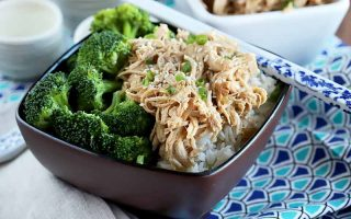 Horizontal image of a brown dish with broccoli florets and shredded chicken with white chopsticks.