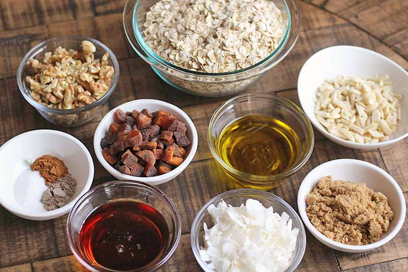Oblique overhead shot of glass and ceramic bowls of oats, walnuts, almonds, coconut, dried apricots, maple syrup, salt and spices, olive oil, and light brown sugar, on a brown wood surface.