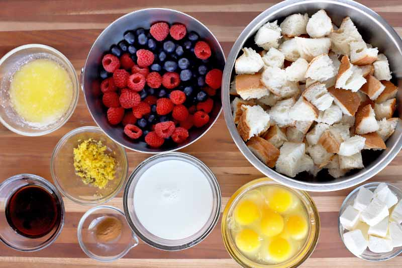 Overhead horizontal image of glass and metal bowls of melted butter, lemon zest, vanilla extract, cinnamon, milk, eggs without their shells, fresh berries, cubed bread, and cubed cream cheese, on a wood surface with horizontal stripes.