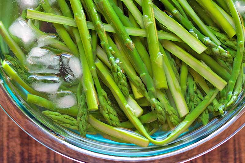 Closely cropped overhead image of a large glass bowl of blanched asparagus in an ice bath, on a brown wood surface.