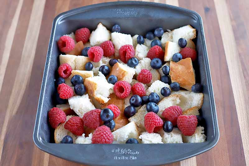 Horizontal image of a metal baking pan of cubed bread and fresh berries in a beaten egg mixture, on a wood surface.
