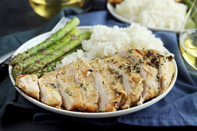 Horizontal image of a white plate with sliced and marinated grilled chicken with fresh asparagus and white rice.