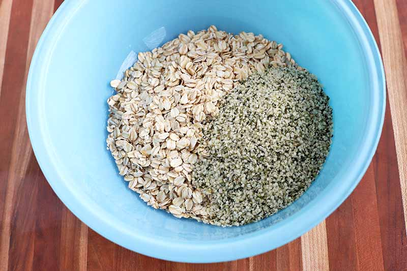Horizontal image of oats and hemp seeds in a blue bowl.
