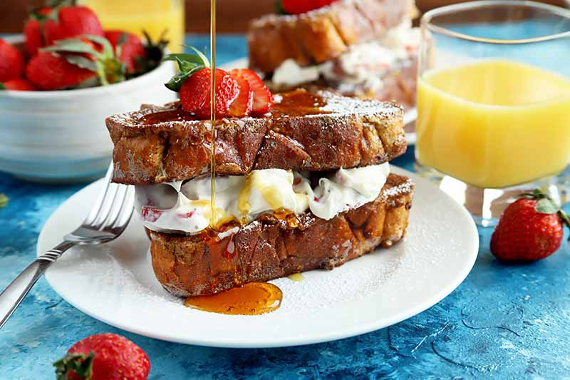 Horizontal image of stuffed French toast on a white plate with maple syrup being poured over it.