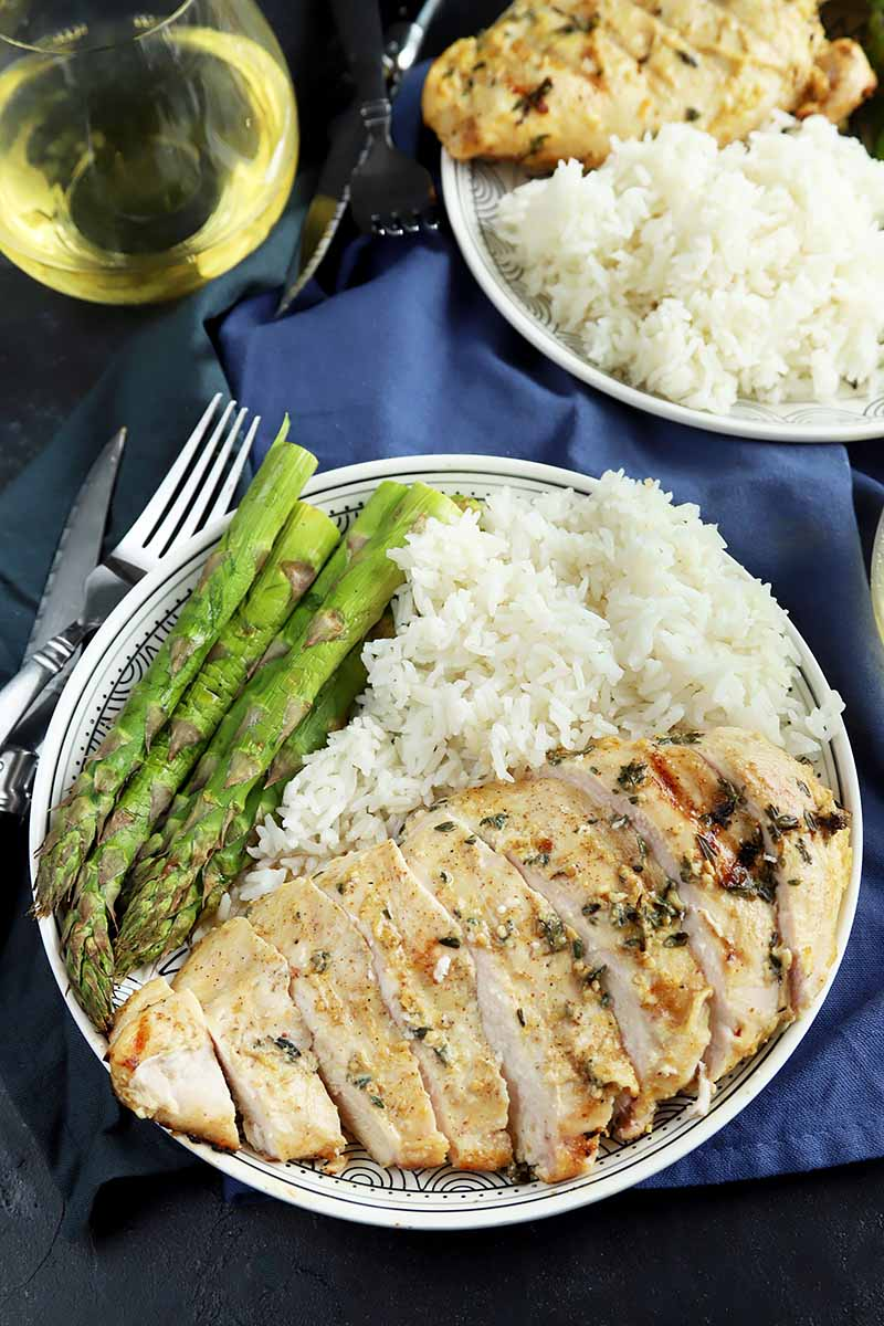 Vertical image of a plate with one sliced and seasoned chicken breast with prepared asparagus and white rice, next to silverware and a glass of white wine on a dark blue napkin.
