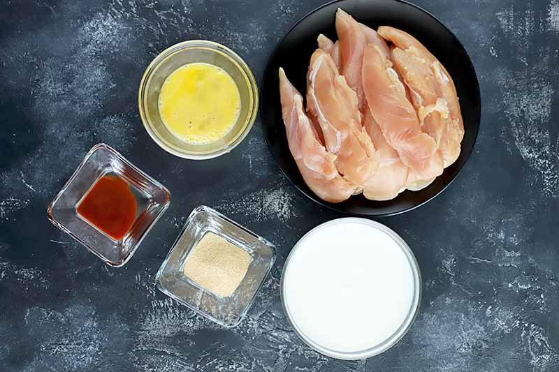Horizontal image of bowls of unbaked chicken, buttermilk, and eggs.