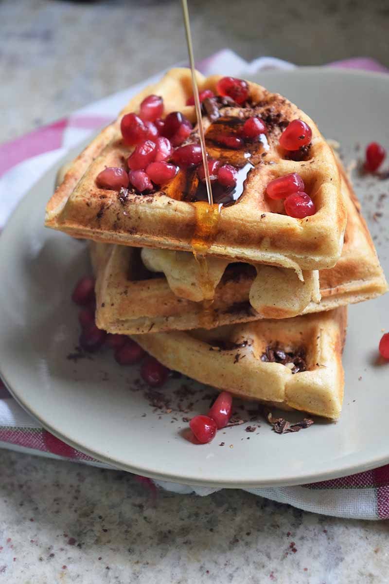 Vertical image of a stack of waffles with pomegranate seeds and syrup being poured over them.