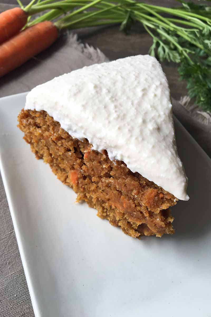 Vertical image of a slice of simple carrot cake with white frosting on a white plate.