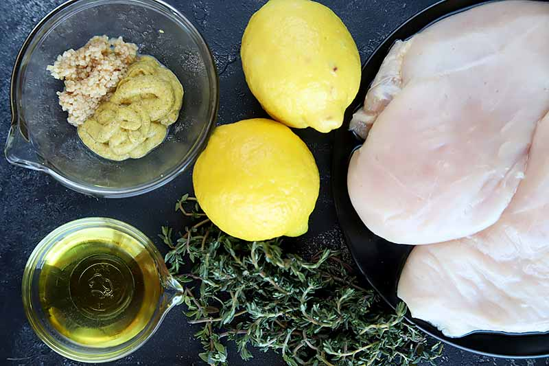 Horizontal image of lemons, herbs, condiments, and raw chicken breast on a dark surface.