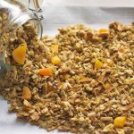 A glass swingtop jar of homemade granola is spilling onto a white parchment paper surface.