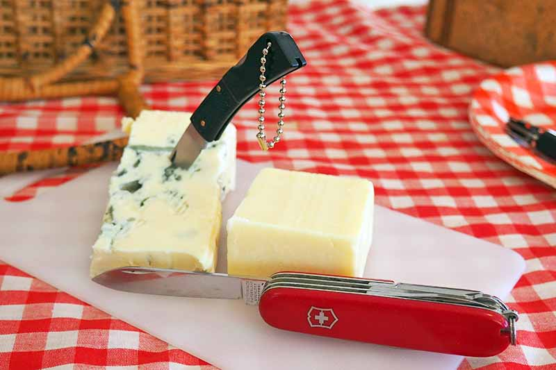 Two knives for cutting cheese on top of a cutting board. A checkered blanket and picnic basket are in the background.
