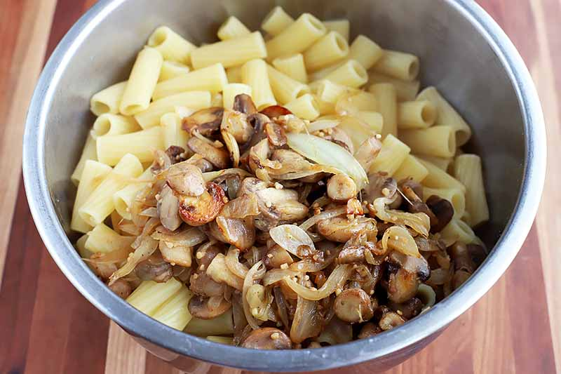 Horizontal image of cooked pasta next to cooked mushrooms in a metal bowl.