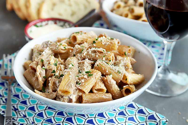 Horizontal image of a white bowl with rigatoni on a blue patterned napkin next to bread slices and a glass of red wine.