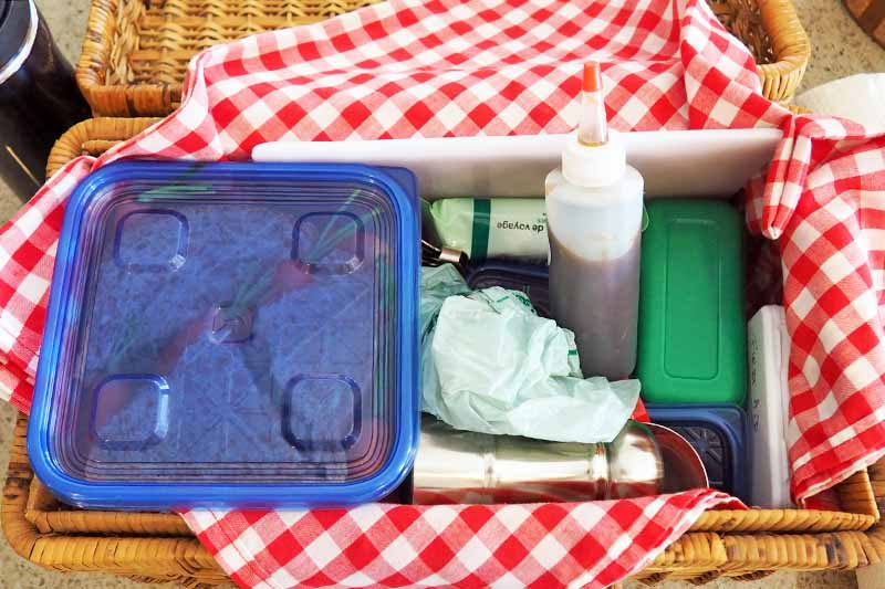 A picnic basket filled with food, condiments, a first-aid kit, and clean-up items.