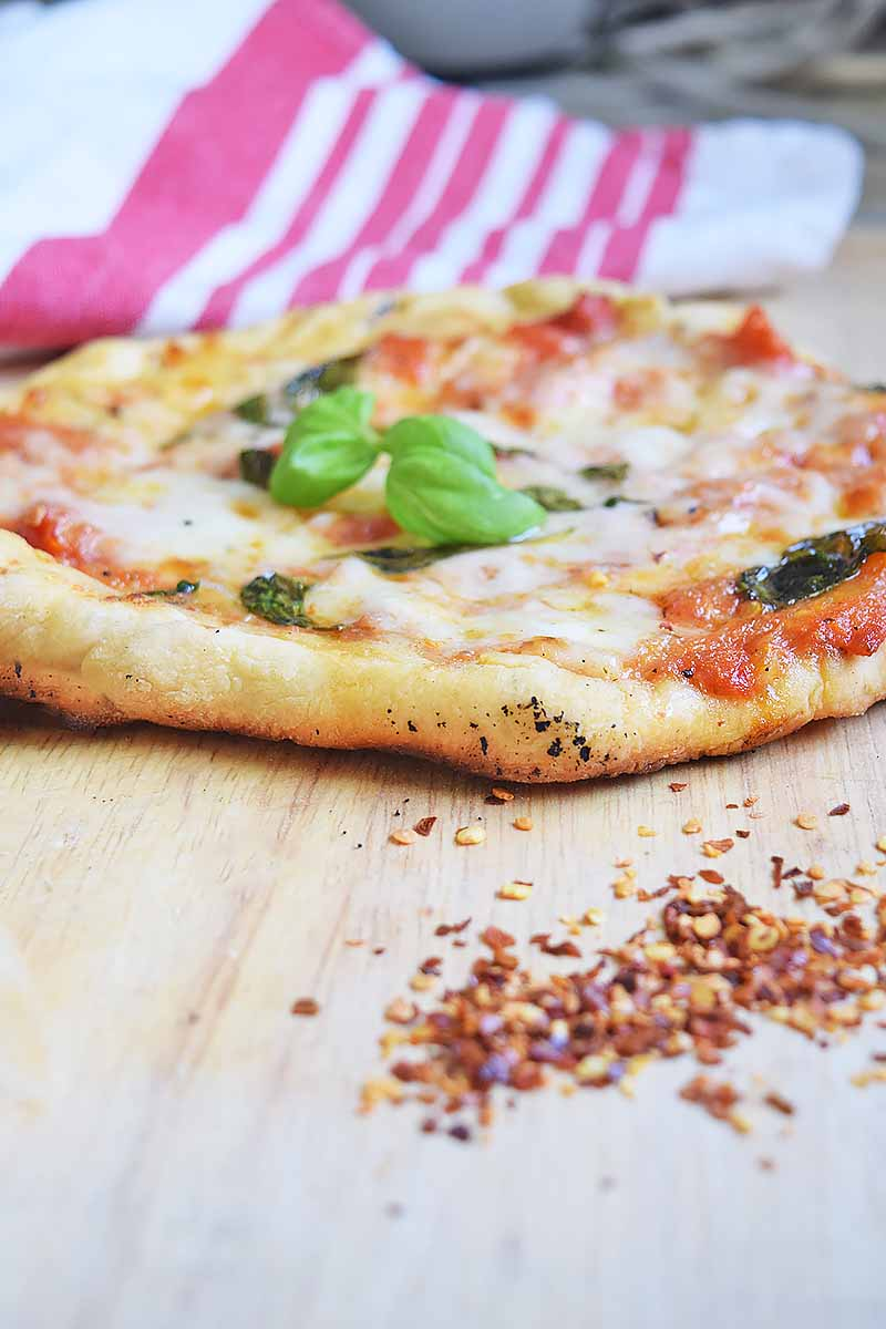 Vertical image of a baked pizza with cheese, sauce, and fresh basil on a wooden table next to a pile of red pepper flakes and a towel.