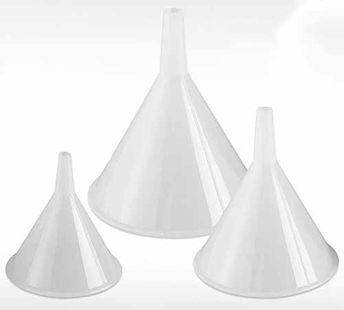 Three different sized plastic funnels isolated on a white background.