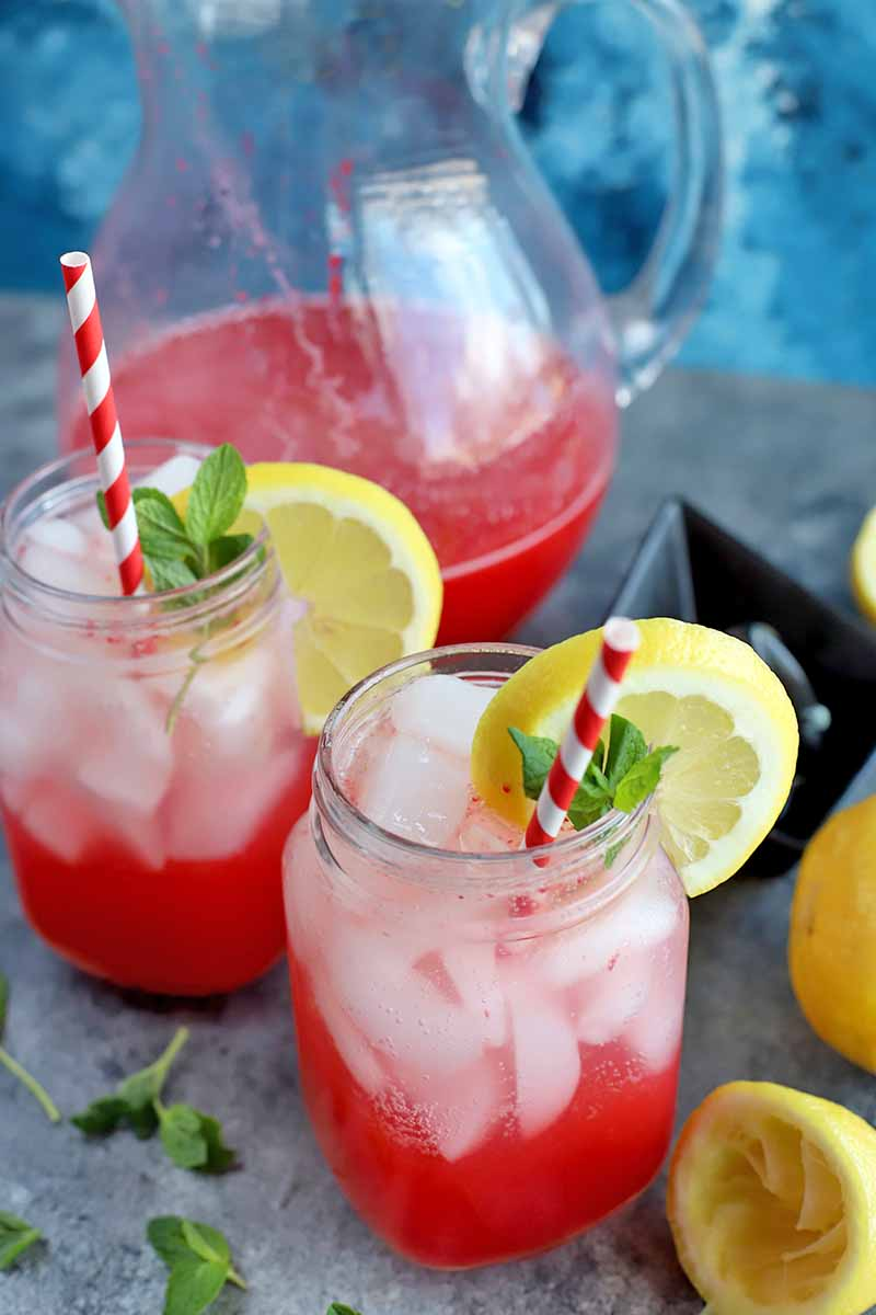 Vertical oblique image of raspberry lemonade in a glass pitcher and two Mason jars, with pink and white straws, citrus garnish, and fresh mint, on a gray surface with a mottled blue background.