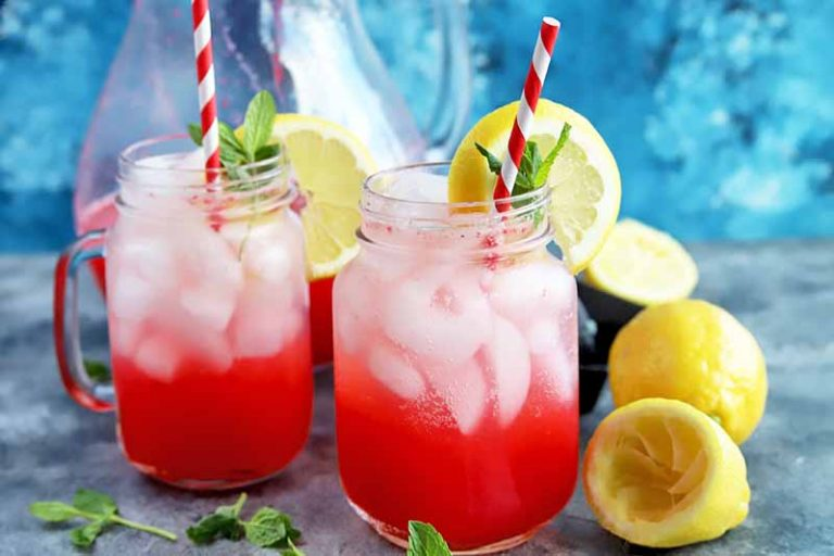 Horizontal image of two Mason jars of raspberry lemonade with ice, with red and white straws, lemons, and mint, with a glass pitcher in the background against a blue wall, on a gray surface.