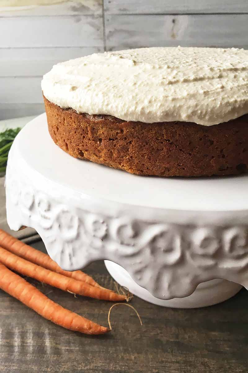 Vertical image of a one-layered orange cake topped with white icing on a white stand next to three carrots.
