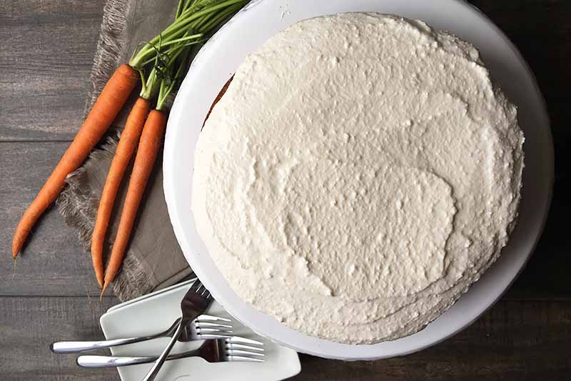Horizontal top-down image of a frosting-covered dessert on a white plate next to fresh carrots and forks.