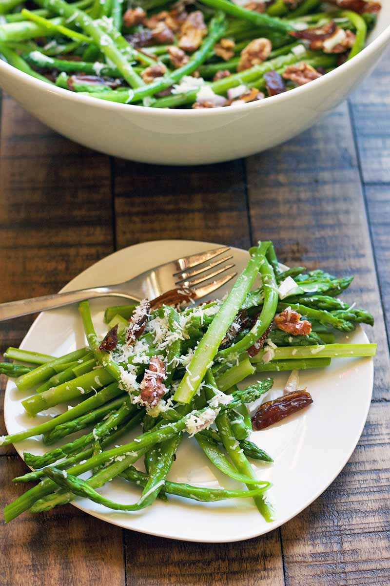 Vertical oblique overhead image of a white plate and a bowl of fresh green springtime vegetable stalks with grated cheese, walnuts, and chopped pitted dates, with a fork, on a wood table.