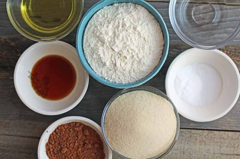 Overhead horizontal closely cropped image of glass, white ceramic, and blue ceramic bowls of oil, vanilla, cocoa powder, flour, sugar, vinegar, and baking soda for baking a cake, on an unfinished wood surface.