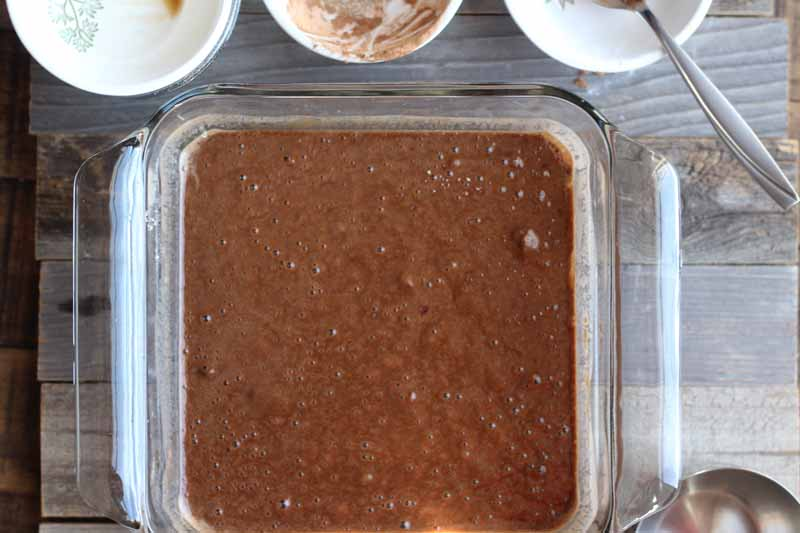 Overhead horizontal image of chocolate cake batter in a square glass baking dish with three small white bowls of ingredients at the top of the frame, with the handle of a spoon sticking out of the leftmost one, on an unfinished wood surface.