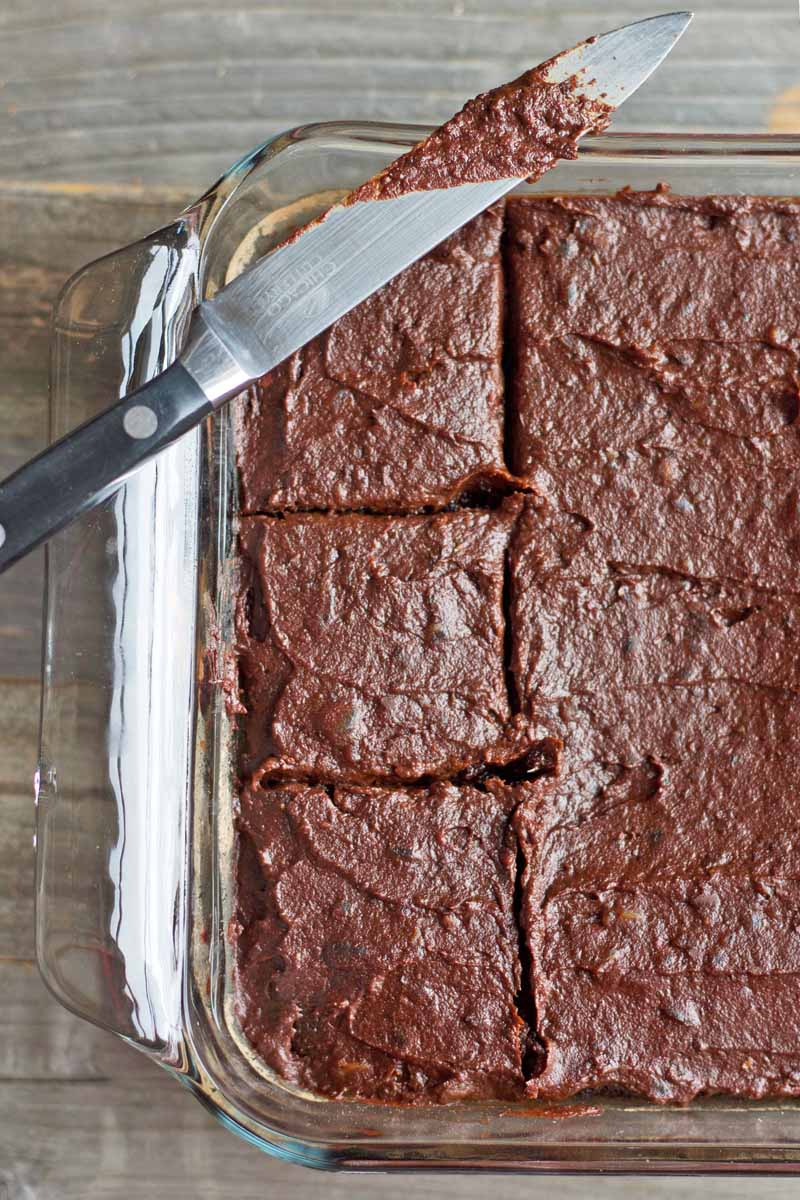 Overhead closely cropped horizontal image of a frosted and sliced chocolate cake in a square glass baking dish, with a knife covered in chocolate icing resting on the rim, on an unfinished weathered wood surface.