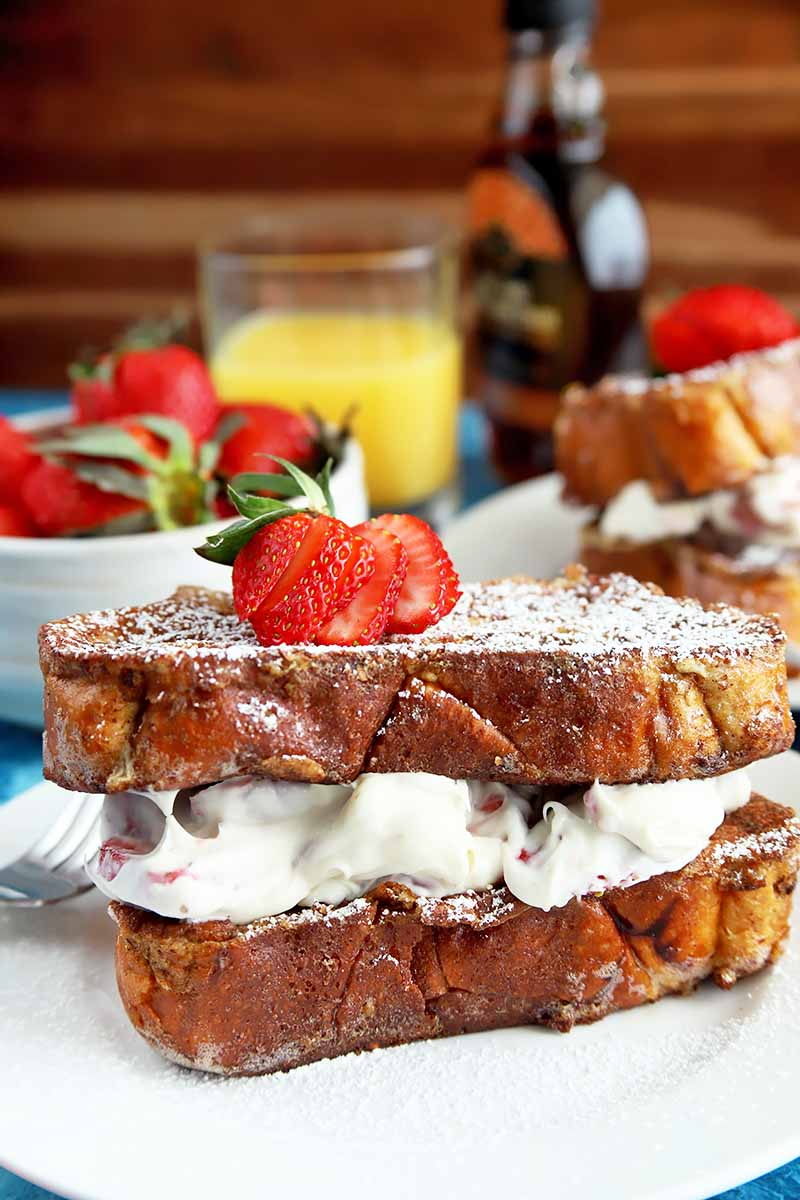 Vertical image of a layered French toast dish with a creamy filling, in front of strawberries and orange juice.