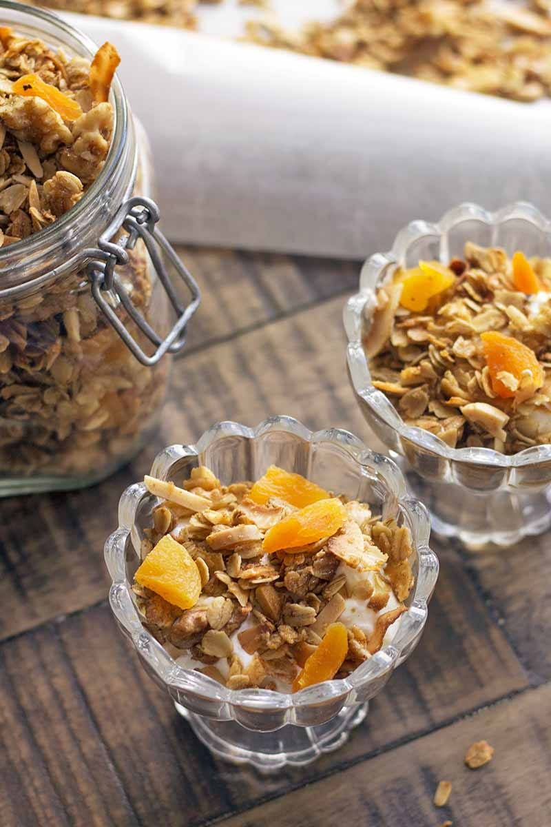 Vertical closely cropped overhead slightly oblique image of two parfait glasses and a swingtop jar of homemade apricot granola, with more in the background on top of a piece of folded parchment paper, on a brown wood table.
