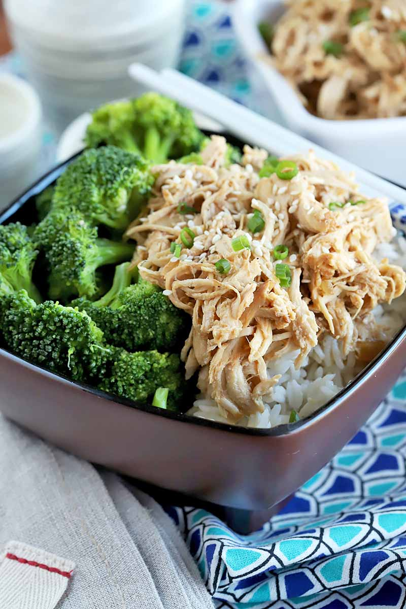 Vertical close-up image of a dark bowl with broccoli and shredded chicken on a blue patterned napkin.