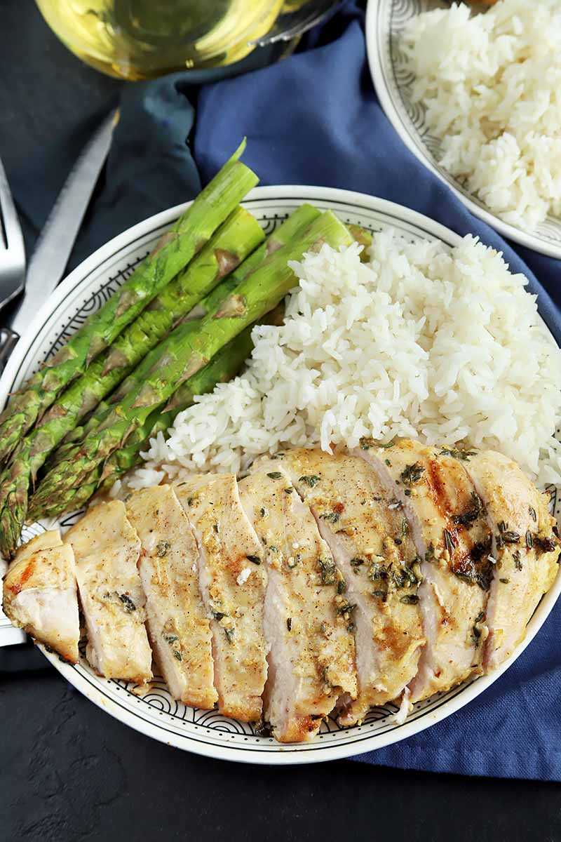 Vertical image of a sliced whole chicken breast on a plate with asparagus and white rice on top of a blue napkin.